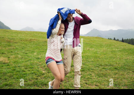 Young couple running down hill holding up anorak in rain, Sattelbergalm, Tyrol, Austria - Stock Photo