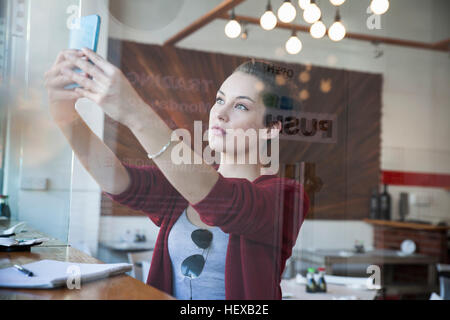 Young woman sitting in cafe, taking selfie, using smartphone - Stock Photo