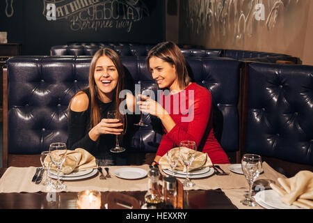 two young beautiful woman relaxing in the restaurant and drinking wine - Stock Photo
