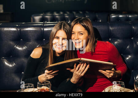 two young beautiful women sitting in a restaurant with menu and laugh - Stock Photo