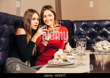 two beautiful young women saw something in the restaurant - Stock Photo