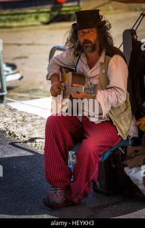 a musician busker playing acoustic guitar at Padstow Harbour in  Cornwall, UK - Stock Photo