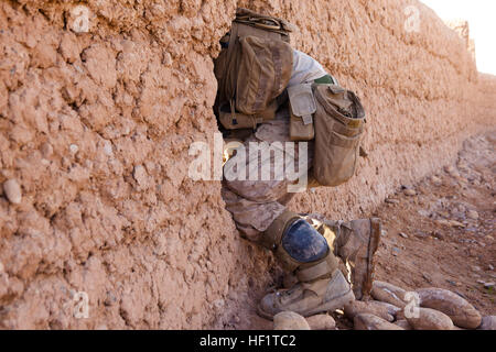 A Marine with 1st Battalion, 9th Marines crawls through a hole in a dirt wall during an interdiction operation near - Stock Photo