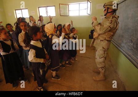 050322-N-5319A-015U.S. Army Chaplin Tommy Fuller takes a photo of Iraqi school children at the Al Mutnba Primary - Stock Photo