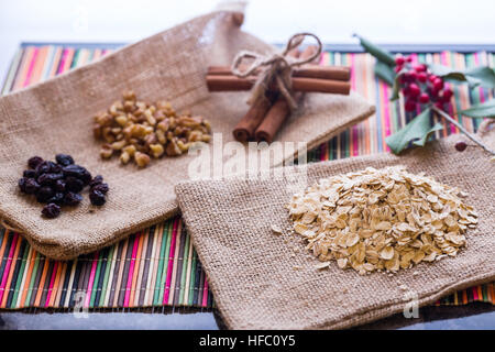 Oatmeal with raisins, walnuts, and cinnamon sticks. - Stock Photo