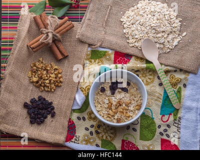 Oatmeal in milk with ingredients of raisin, walnut, cinnamon sticks. - Stock Photo