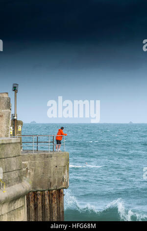 A man standing on the quayside overlooking the entrance to Newquay Harbour in Cornwall, England, UK. - Stock Photo