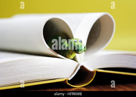 Opened book, bookworm peeking out from pages shaped to form a heart - Stock Photo