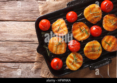 Tasty roasted new potatoes and tomatoes with rosemary close up on a grill pan. horizontal view from above - Stock Photo