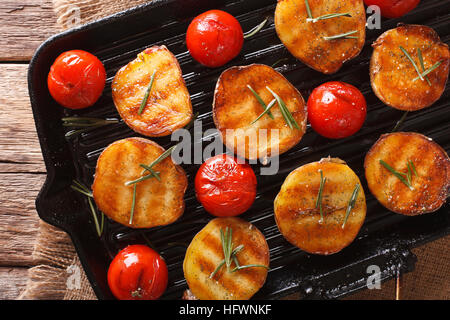 grilled potato halves and tomatoes with herbs macro on the grill pan. horizontal view from above - Stock Photo