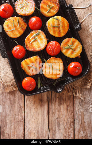 Tasty roasted new potatoes and tomatoes with rosemary close up on a grill pan. vertical view from above - Stock Photo