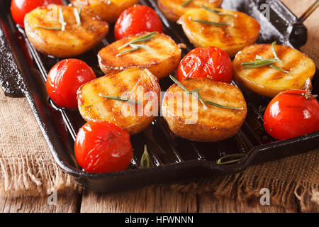 roasted new potatoes and tomatoes with rosemary close up on a grill pan. Horizontal - Stock Photo