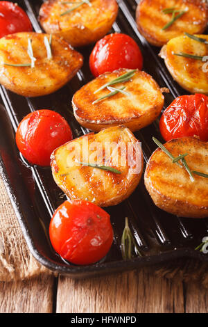 roasted new potatoes and tomatoes with rosemary close up on a grill pan. vertical - Stock Photo