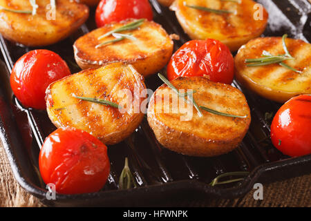 Grilled new potatoes and tomatoes with rosemary macro on the grill pan. Horizontal - Stock Photo