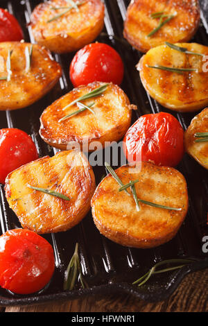 Grilled new potatoes and tomatoes with rosemary macro on the grill pan. vertical - Stock Photo