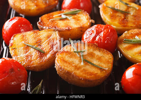 grilled potato halves and tomatoes with herbs macro on the grill pan. horizontal - Stock Photo