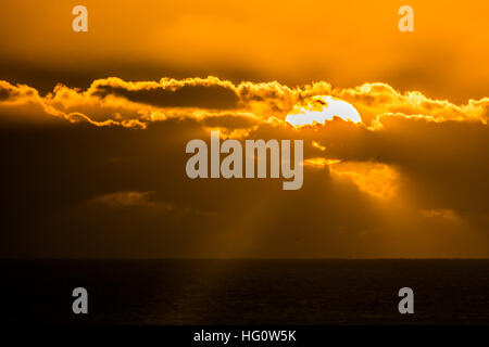 Sennen Cove, Cornwall, UK. 2nd January 2017. UK Weather. After a fine and sunny day the sun sets behind low clouds - Stock Photo
