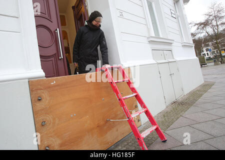 Luebeck, Germany. 04th Jan, 2017. Resident Uta Hansen stands behind a wood panel erected by renters for flood protection - Stock Photo