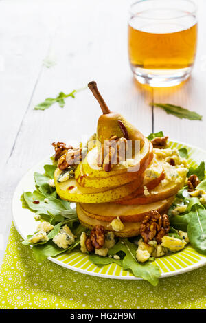 Fruit salad, whole pear sliced,  walnuts caramelized in honey, blue cheese and arugula. Green plate on white wooden - Stockfoto