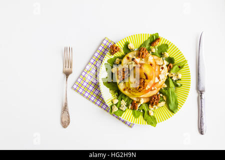 Fruit salad, whole pear sliced,  walnuts caramelized in honey, blue cheese and arugula. Green plate on white table, - Stockfoto