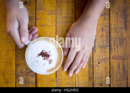 Woman hands holding coffee cup of hot cappuccino on vintage wood table. - Stock Photo