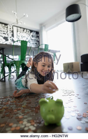 Smiling girl depositing coins into piggy bank on hardwood floor - Stock Photo