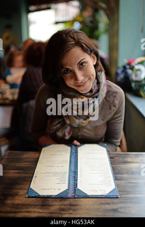 Young attractive woman looking at menu in a cafe - Stock Photo