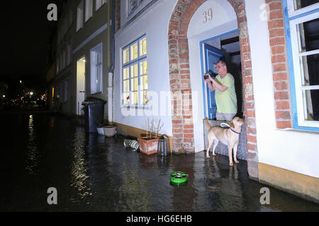 Luebeck, Germany. 04th Jan, 2017. A local resident photographs a flooded street in Luebeck, Germany, 04 January - Stock Photo