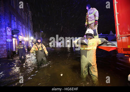 Luebeck, Germany. 04th Jan, 2017. Members of a local fire brigade distribute sandbags in Luebeck, Germany, 04 January - Stock Photo