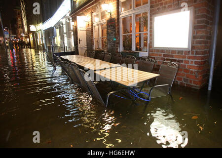 Luebeck, Germany. 04th Jan, 2017. Tables and chairs on a flooded sidewalk in Luebeck, Germany, 04 January 2017. - Stock Photo