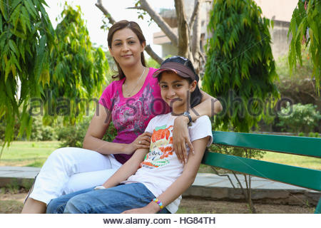 Woman with her daughter sitting on a bench in a park - Stock Photo