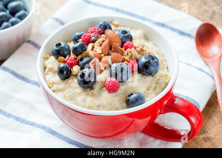 Oatmeal porridge with fresh blueberries, raspberries and almonds in red bowl on white table cloth. Healthy breakfast - Stock Photo