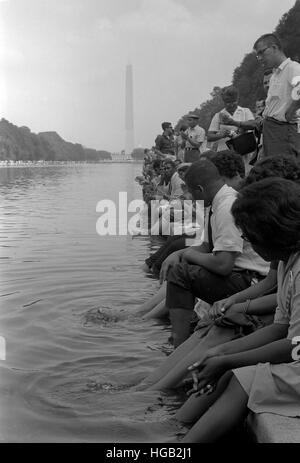 Demonstrators sit along the Reflecting Pool during the March on Washington, 1963 - Stockfoto