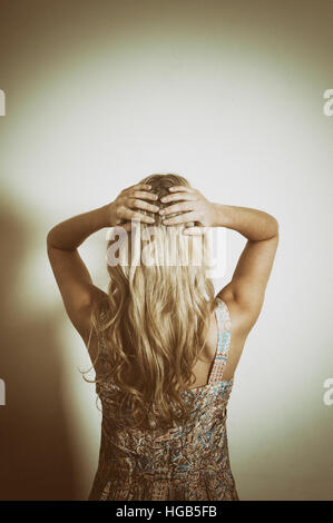 Rear view of a woman hands on head - Stockfoto
