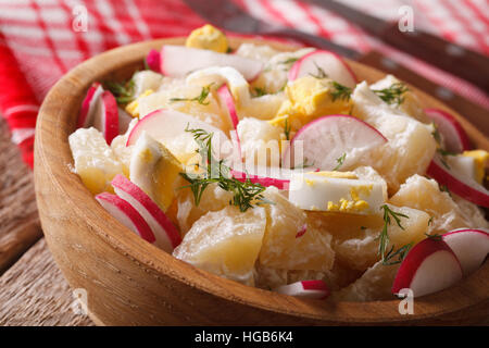 potato salad with radish and eggs close-up on a plate on the table. horizontal - Stock Photo
