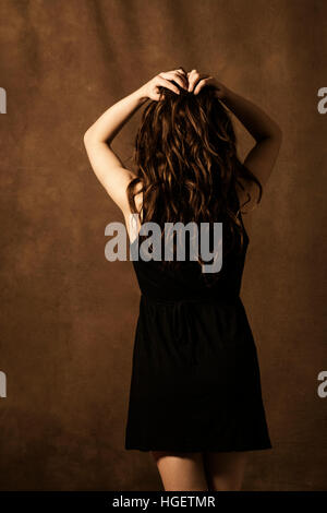 Rear view of a stressed woman hands on head - Stock Photo