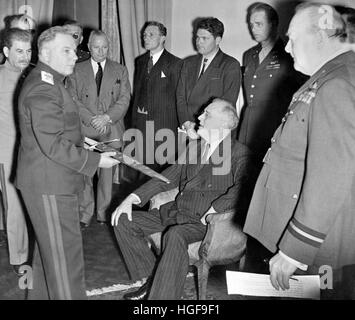 President Roosevelt is presented with the Stalingrad Sword at the Tehran Conference. Churchill and Stalin look on. - Stock Photo