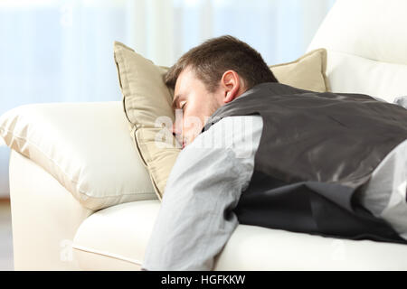 Tired businessman sleeping lying on a couch after work at home - Stock Photo
