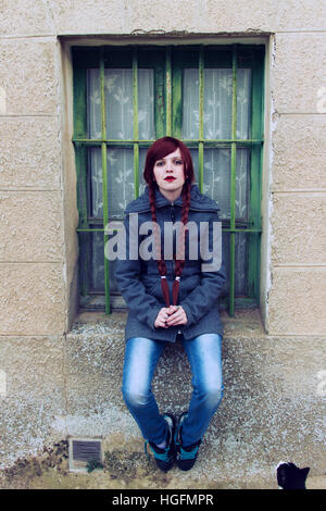 Young redhead woman, with two long braids, sitting near a old window - Stock Photo