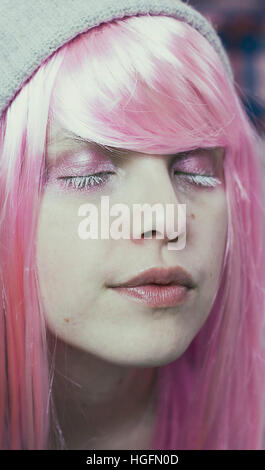 Portrait of a young woman with pink hair and her eyes closed like she's dreaming - Stock Photo