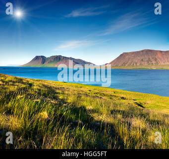 Typical Icelandic landscape with volcanic mountains and pure water river. Sunny summer morning in the west coast - Stock Photo