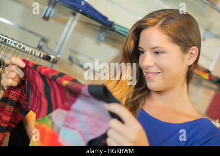 Lady holding modern top in clothes shop - Stock Photo
