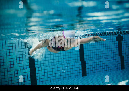 Underwater shot of female swimmer in action inside swimming pool. Young woman training in the pool. - Stockfoto