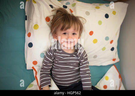 smiling Kid boy lying on the bed with his eyes closed, playing with sleep, lifestyle, real interior, soft focus - Stock Photo