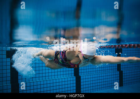 Underwater shot of young sportswoman swimming in pool. Female swimmer in action inside swimming pool. - Stock Photo