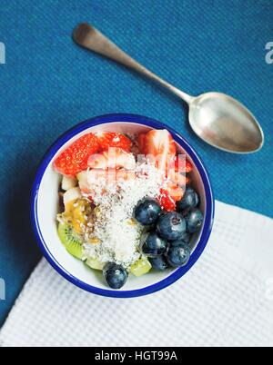 Breakfast Fruit Salad Bowl. Healthy breakfast option for any age. Antique cutlery, ceramic blue and white bowl. - Stock Photo