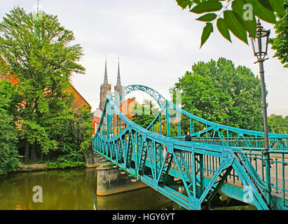The Tumski bridge over the Oder River leads to the Wroclaw Cathedral with high Gothic spires - Stock Photo
