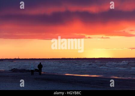 Couple walking at sunset golden hour in Kauguri Jurmala Latvia - Stock Photo
