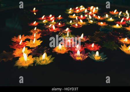 Close focus on colorful candles with fire floating on oil pool in low key tone. People float candles for lucky wishing. - Stock Photo