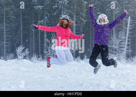 Ukraine Bukovel December 17, 2015 Girls jumping. Two funny girls jump in the snow against beautiful forest in Bukovel, - Stockfoto